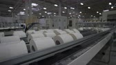 уборная : camera moves slowly along long conveyor with toilet paper under manufacturing process on factory