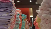 ношение : closeup lines with neatly folded new stylish bright colors clothes at big light fashion store
