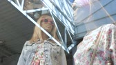 организованный : camera moves to mannequins wear in new stylish designers clothes at big glamor store glass case