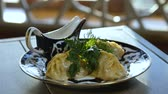 receptek : closeup person hands put blue-white plate with Tatar patty manty dumplings and sauce-boat with sour cream on white table Stock mozgókép