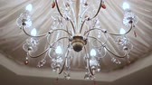 reflexo : closeup large brilliant lustre with eight lamps under white decorated carved ceiling