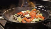 chef quipe : closeup person shakes large black pan with frying vegetables above gas stove open flame against dark background