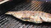 chef quipe : slow motion macro delicious fried fresh grill fish with golden crust sprinkled with fragrant spice