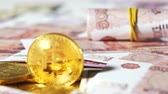 become : golden coins to virtual cryptocurrency bitcoin becoming popular all over the world near rubles Stock Footage