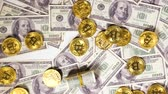 parasal : slow motion mined golden coins created by valuable resource bitcoin used as virtual currency fall on banknotes Stok Video