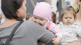tart : KAZAN, TATARSTAN  RUSSIA - SEPTEMBER 18 2017: Close up of a backside view of a young brunette woman holding a cute baby in pink clothes in mall against people on September 18 in Kazan