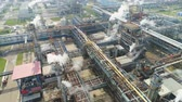 petrochemical plant : flycam rotates and shows huge gas and oil refinery plant with pipelines workshops and towers in white smoke Stock Footage