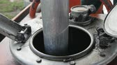 petrochemical : closeup special metal tool with water drops put into metal reservoir in petroleum refinery plant yard