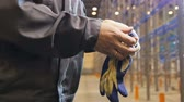 rack focus : slow motion closeup worker in gray uniform stands on blue-white gloves against flow focus metal racks in warehouse