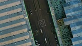 helipad : aerial view helicopter landing pad on road with driving lorries between large warehouses with metal roofs Stock Footage