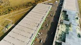 helipad : drone moves slowly over large warehouse buildings with helipad at wide yard among green meadows