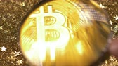 loupe : closeup view through loupe on the famous cryptocurrency bitcoin model among the gold sand against the light rays Stock Footage