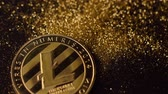 litecoin : macro fantastic glowing litecoin real model falling down on gold sparkles pile and dust flies around