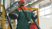 petrochemical : backside view worker in green uniform with cross body bag lifts up metal ladder at gas and oil refinery plant