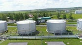 szintetikus : aerial view industrial plants workers walk past numbered huge tanks with flammable liquid in countryside