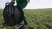 шпуля : side view skilled worker in green uniform large black bobbin with cable electric wire along meadow