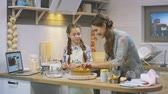jantar : KAZAN, TATARSTAN  RUSSIA - FEBRUARY 14 2018: Slow motion closeup joyful mother and daughter with long plaits have fun in kitchen preparing festive dinner for family on February 14 in Kazan