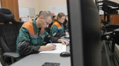 kontrol listesi : KAZAN, TATARSTAN  RUSSIA - SEPTEMBER 27 2017: Closeup gas company staff in uniforms sits at computers controlling oil processing and writes down in list on September 27 in Kazan