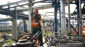 petroquímico : KAZAN, TATARSTAN  RUSSIA - AUGUST 22 2017: Skilled employee in orange vest controls tank filling with oil on August 22 in Kazan