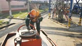 petroquímico : KAZAN, TATARSTAN  RUSSIA - AUGUST 22 2017: Person in orange helmet and protective glasses closes and seals cistern cap on technical ground on August 22 in Kazan