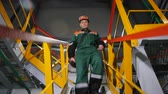 refinaria : KAZAN TATARSTAN  RUSSIA - AUGUST 21 2017: Closeup man in protective outfit climbs down stairs from workshop in oil production factory on August 21 in Kazan