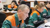 нефтехимический : KAZAN TATARSTAN  RUSSIA - AUGUST 21 2017: Closeup of petrochemical factory staff in uniforms sits at computers controlling oil processing and writes down on list on August 21 in Kazan