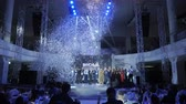 hostia : KAZAN, TATARSTAN  RUSSIA - MARCH 14 2018: Celebration guests sit at tables watching performance and confetti flies above festival hosts on March 14 in Kazan