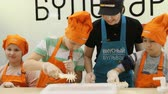 мастер : KAZAN, TATARSTAN  RUSSIA - MARCH 14 2018: Closeup of concentrated children prepare dough using mall on March 14 in Kazan