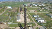oil industry : upper view high tower on oil processing factory territory with industrial buildings against beautiful landscape