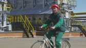 técnico : KAZAN, TATARSTANRUSSIA - APRIL 04 2018: Engineer in green work outfit rides slowly cycle along powerful industrial furnaces against blue sky on April 04 in Kazan