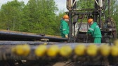 shale : KAZAN, TATARSTAN  RUSSIA - APRIL 17 2018: Petroleum workers in green uniforms and orange helmets fix drilling rig against trees on April 17 in Kazan