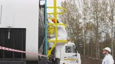 shale : KAZAN, TATARSTAN  RUSSIA - APRIL 17 2018: Closeup worker in white uniform and respirator climbs up gas reservoir placed on truck platform on April 17 in Kazan