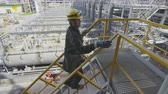 petrochemical : worker goes up stairs onto support ground by pipes Stock Footage