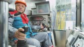 shale : Serious Worker Sits in Cabin Operates Drilling Rig