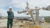 shale : Employee Stands near Pipe Structure Talks on Radio Stock Footage