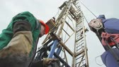 shale : Plant Workers Control Drilling Rig Hook Lowering Stock Footage