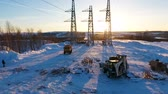 electricity pole : towers and construction machinery on ground with snow Stock Footage