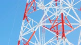 케이블 : red and white lacy metal transmission tower against sky