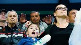 hóquei : slow motion woman with son supports team against fan waving to camera