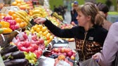 káposzta : women do shopping of vegetables fruits from stalls on city market Stock mozgókép