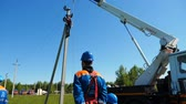 transformatör : slow motion worker controls crane lifting wires to pole in village