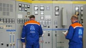 tensão : engineers stand at network power cabinets controlling readings Vídeos