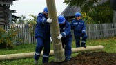 electricity pole : employees hold concrete pole transported to ground pit