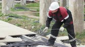 bobina : employee uncoils wire at electrical substation site