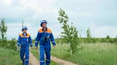 electricity pole : electricians walk along track under high voltage power lines Stock Footage