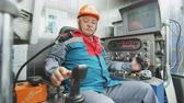 well site : middle-aged driver controls drilling machine in modern cabin Stock Footage