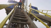 fosilní : worker goes down steps from exploratory drilling machine high platform