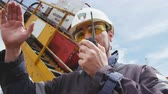 well site : engineer stands by exploratory drilling machine speaks over radio Stock Footage