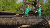 well site : workers take pipe from truck platform insert into drilling machine by forest
