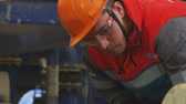 well site : worker in helmet protective glasses uniform with logo does job Stock Footage